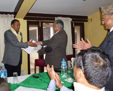 Khageshwaar Sharma and Prof Dhakal exchange the renewed MOU documents