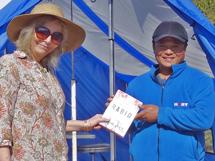 Barbara Webb presenting Chandra Rai, HART's Community Liaison Officer, with a copy of 'Rabid' on behalf of Olivia Stuart
